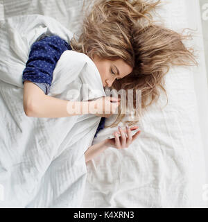 Morning, the woman under the blanket, turns off the alarm clock or watching the social network - Stock Photo