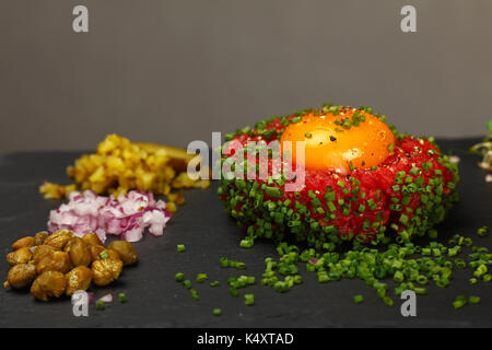 One portion of raw minced beef meat tartare steak with egg yolk, green chive, onions, cucumbers and capers on black - Stock Photo