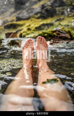 Woman bathing in a hot spring in Iceland, in the Landmannalaugar mountains, view of the feet. - Stock Photo