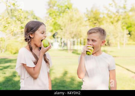 children eating apples - Stock Photo