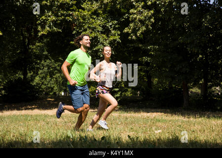 Young couple running in nature on a sunny summer day - Stock Photo
