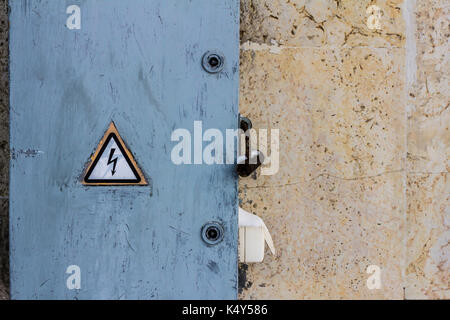 electrical hazard sign placed on a  locked electric power dashboard on a scratched painted wall - Stock Photo