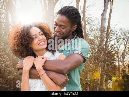 Digital composite of Couple embracing against blurry trees with flare - Stock Photo