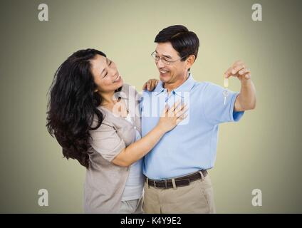 Digital composite of Couple Holding key in front of vignette - Stock Photo