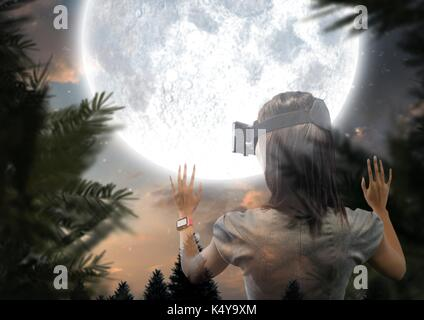 Digital composite of woman with VR glasses forest at night with big moon - Stock Photo