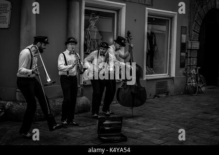 Street musicians playing in a narrow alley in the old city of Graz, Austria, in black and white. - Stock Photo