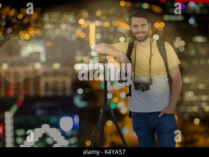Digital composite of happy photographer rest on tripod in front of the city at night ( with blurred lights) and - Stock Photo