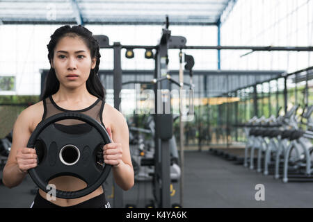 young woman bodybuilder execute exercise in fitness center. female athlete lift heavy weight barbell plate in gym. - Stock Photo