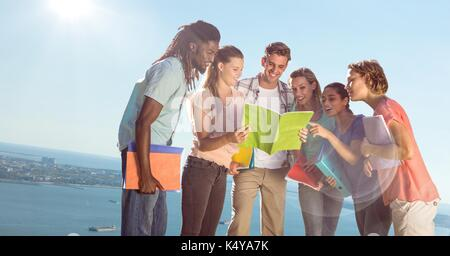 Digital composite of College students against blurry slanted coastline - Stock Photo