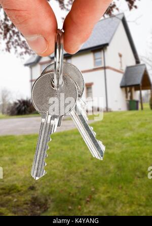 Digital composite of Hand Holding key in front of house - Stock Photo