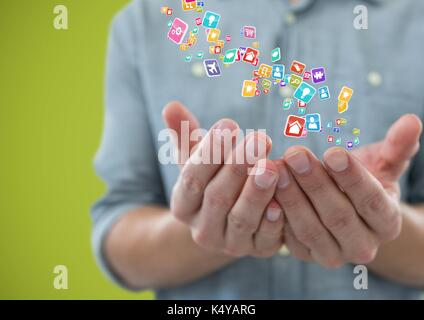 Digital composite of hands  with application icons over. Green background - Stock Photo