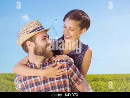 Digital composite of Couple piggy back in field on summer day - Stock Photo