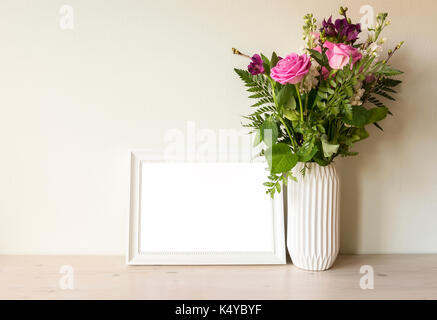 Empty frame mockup with flower bouqet in vase. - Stock Photo