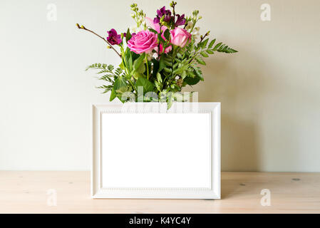 Empty white frame mockup with flower bouquet in vase. - Stock Photo