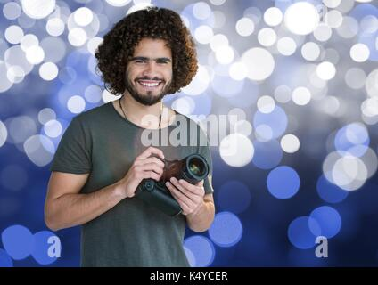 Digital composite of photographer with camera on hands. Blue and white bokeh background - Stock Photo