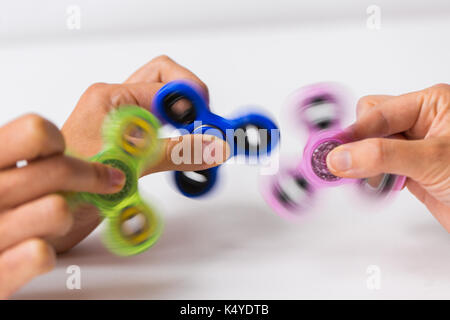 close up of hands playing with fidget spinners - Stock Photo