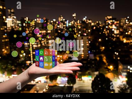 Digital composite of hand with applications icons cube on it. Blurred city at night - Stock Photo