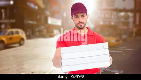 Digital composite of Delivery man with pizza boxes against blurry street with flare - Stock Photo