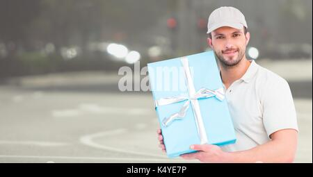Digital composite of Delivery man with blue gift against blurry street - Stock Photo