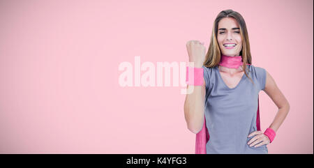 Portrait of cheerful woman in superhero costume while standing against pink background - Stock Photo