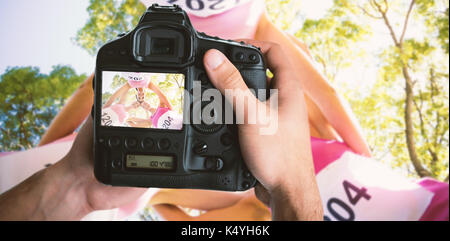 Cropped image of hands holding camera  against young athlete women forming huddles - Stock Photo