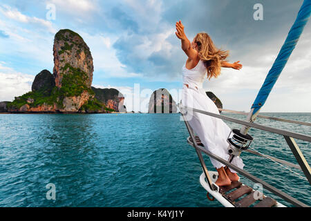 Joyful young woman portrait. Happy girl stand on deck of sailing yacht, have fun discovering islands in tropical - Stock Photo