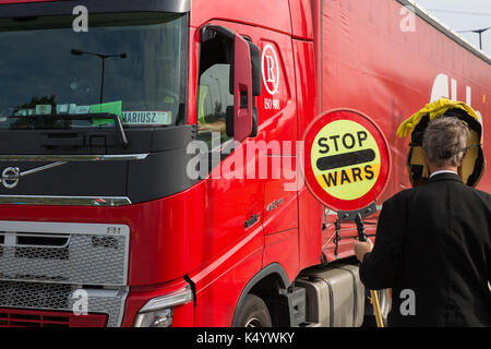 London, UK. 7th Sep, 2017. An anti-war campaigner tries to engage with the driver of a truck carrying military equipment - Stock Photo