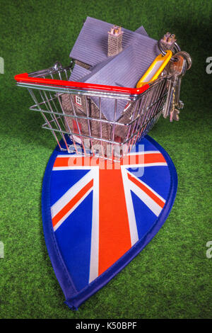 Model house in a model shopping basket, with house keys, on Union Jack colours. A concept to depict the UK housing - Stock Photo