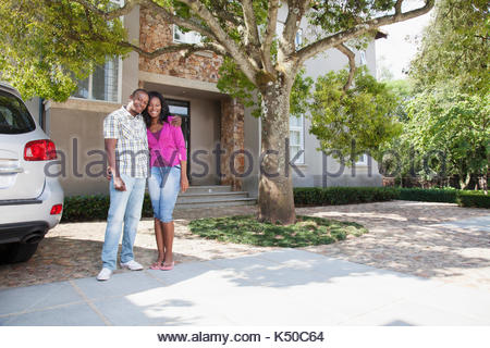 Portrait of couple standing in front of their house - Stock Photo