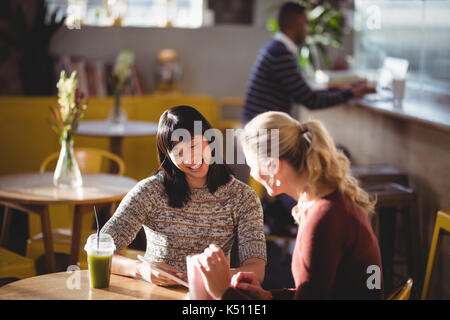 Smiling young female friends using tablet computer at table in coffee shop - Stock Photo