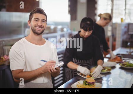 Portrait of smiling waiter standing against female chefs preparing food in kitchen at coffee shop - Stock Photo