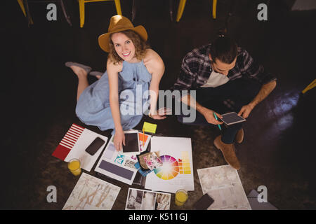 High angle portrait of smiling young female designer sitting by male colleague with sheets on floor at coffee shop - Stock Photo