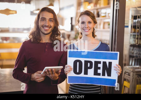 Portrait of smiling waitress holding placard while standing by man with digital tablet at coffee shop - Stock Photo