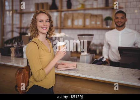 Portrait of smiling young female customer holding disposable coffee cup at counter against waiter in cafeteria - Stock Photo
