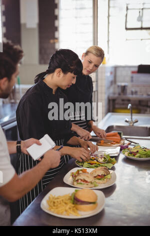 Young female chefs preparing food on kitchen counter at cafeteria - Stock Photo