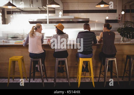 Rear view of friends sitting on stool at counter in coffee shop - Stock Photo