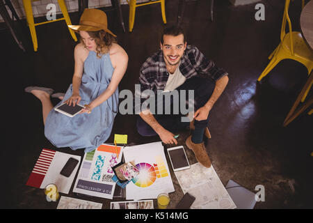 High angle portrait of smiling young male designer sitting by female colleague with sheets on floor at coffee shop - Stock Photo
