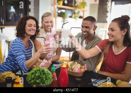 Happy young friends raising drinks while sitting at table in coffee shop