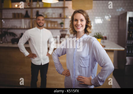 Portrait of smiling young woman with hand on hip against friend standing at coffee shop - Stock Photo