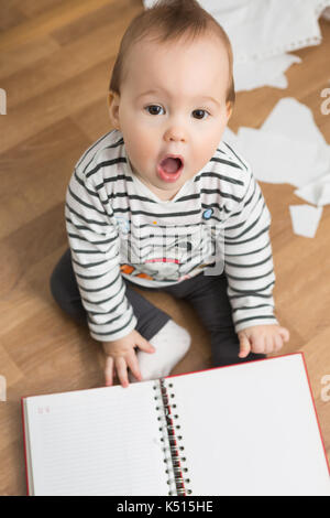 Ten months old baby girl playing with papers and paper folder on the floor; tearing the paper and creating a mess - Stock Photo