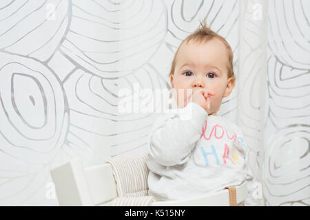 Eleven months old baby girl sitting in a stool making funny faces into the camera and putting her finger in the - Stock Photo