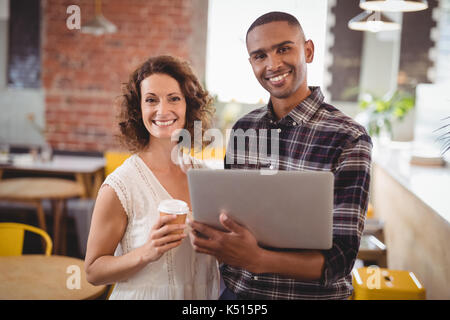 Portrait of smiling young friends standing with disposable coffee cup and laptop at cafeteria - Stock Photo