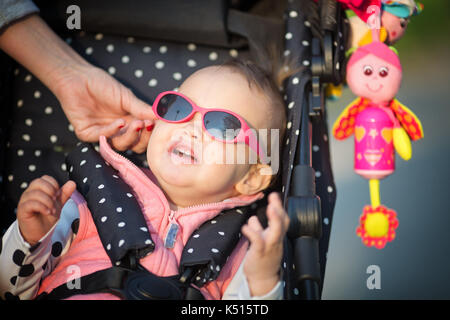 Mother's hand putting sunglasses on the one year old baby girl's head; girl sitting in the dotted stroller - Stock Photo