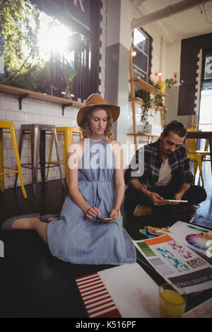 Young professionals using technologies while sitting with sheets on floor at coffee shop - Stock Photo