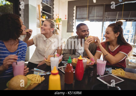 Young friends sharing food at table in coffee shop - Stock Photo