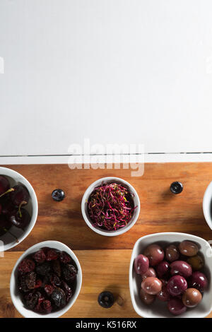 Beetroot slice with various fruits in bowls on cutting board over table - Stock Photo