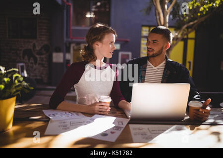 Young creative professionals talking while sitting with laptop at table in coffee shop - Stock Photo