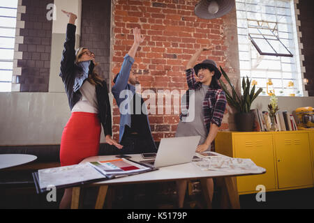 Excited young creative team standing with arms raised at coffee shop - Stock Photo
