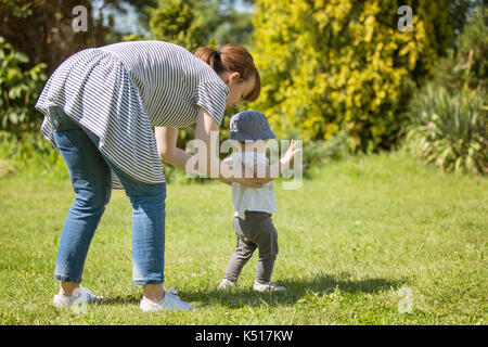 Fourteen months old baby girl making her first steps; walking on her own on the lawn on a sunny day; mother helping - Stock Photo