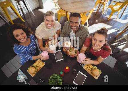 High angle portrait of smiling young friends sitting with lunch at table in coffee shop - Stock Photo